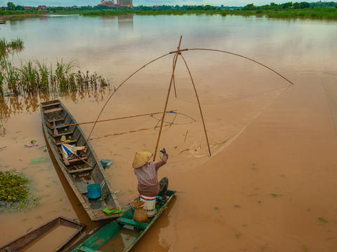Fisherman in the Mekong with ancient fishing tools フォト