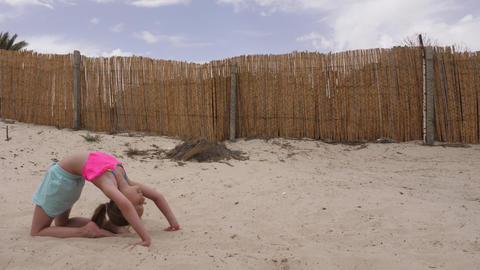 Teenager girl doing acrobatic stunt on sand empty beach. Slow motion GIF