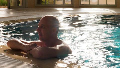 Portrait adult man relaxing in swimming pool near edge in luxury hotel GIF