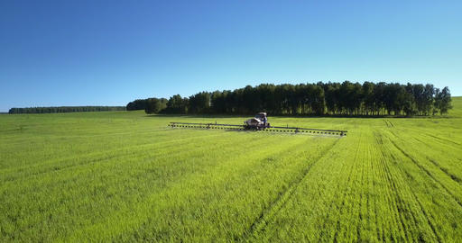 tractor field sprayer with chemicals operates near wood Live Action