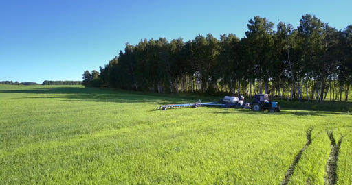 trailed sprayer turns right in trees shadow on green field Live Action