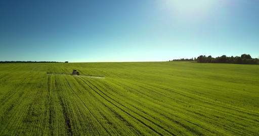 drone moves to and flies over trailed sprayer under blue sky Live Action