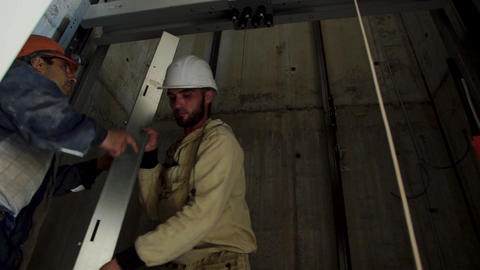Builders working in the Elevator shaft. Workers install Elevator equipment Footage