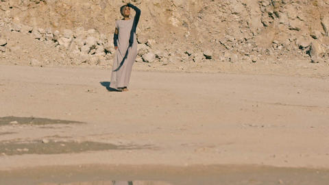 A young attractive woman in ethno-clothes approaches the lake in a hot, sultry Footage