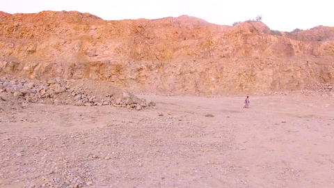 Lonely young woman walking barefoot on the sand in the background of the GIF