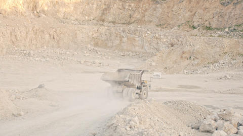 The truck rides in a sandy quarry past a white piano GIF