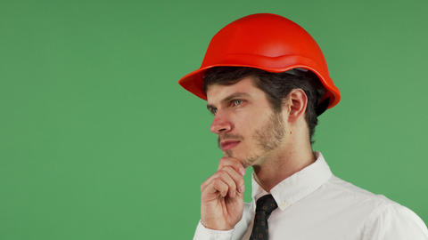 Handsome male constructionist in a hardhat looking away thoughtfully Footage