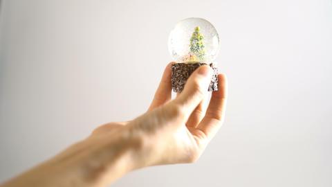 Hand hold Christmas snow globe on white background ビデオ