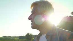 Happy old male farmer looking forward on his field and smiling, beautiful nature Footage