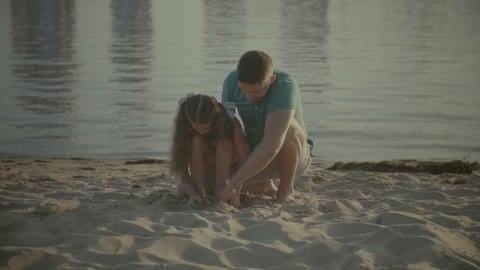 Father and daughter playing in the sand on beach Footage