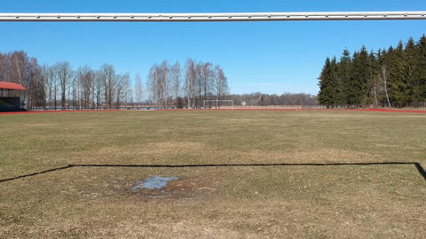 drone fly trough football gate in early spring time, aerial view Footage