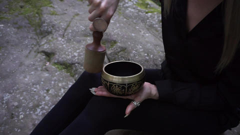 Tibetan singing bowl in the hands of a woman with long nails Footage