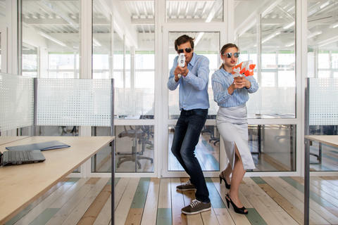 Colleagues with toy guns in office Photo