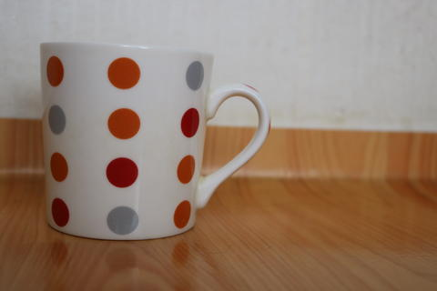 Colorful coffee white mug over wooden floor フォト