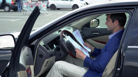 Business man sitting in the car and holding business... Stock Video Footage