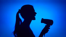 Silhouette of woman having fun singing into hair dryer. Female dancing silly on Footage