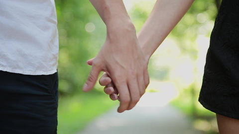 A pair of lovers wearing blue jeans join hands and walk together, close-up Footage