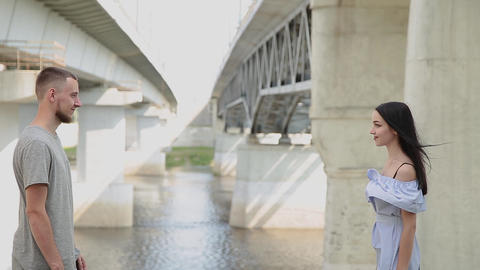 A loving couple are standing under a bridge hugging and kissing ビデオ
