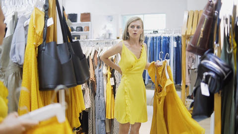 Woman fitting the yellow dress in the Boutique. Fashionable and stylish girl Footage