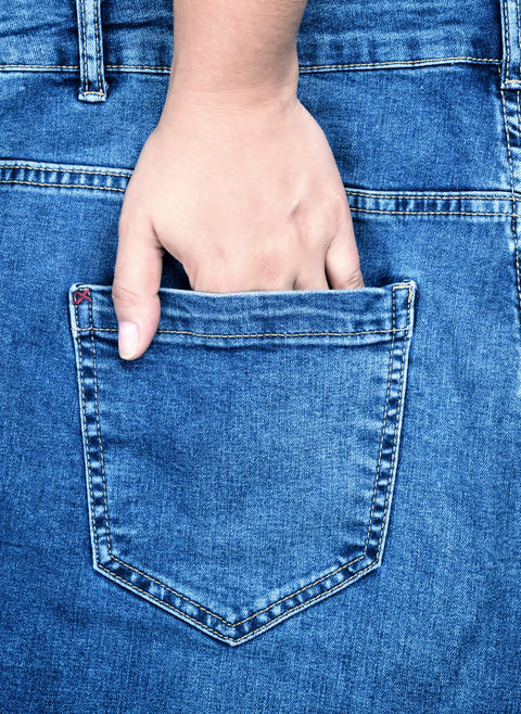 female hand is stuck in the back pocket of blue jeans Photo