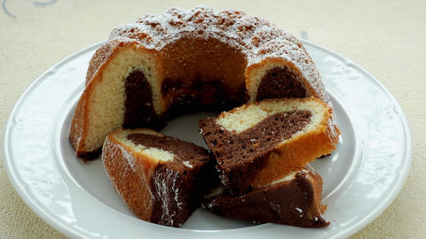 Traditional homemade marble cake. Sliced marble bundt cake on white plate Live Action