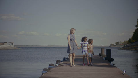 Cheerful family with kids walking along wooden jetty Archivo