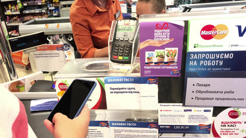 SUMY, UKRAINE - AUG 13, 2018: Customer paying with apple pay by mobile phone on Archivo