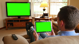 4K Man with Tablet PC Watches Television ビデオ