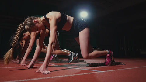 Female runners at athletics track crouching at the starting blocks before a race Footage