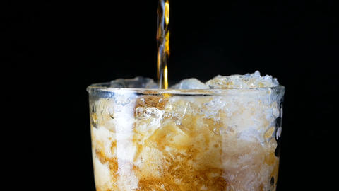 Slow motion pouring cola soda rootbeer mixed water in to the glass with ice GIF