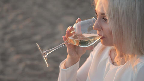 A girl is drinking wine on the beach Footage