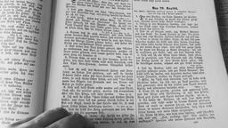 Man is searching through an old german language bible Footage