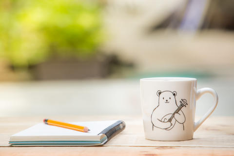 pencil, notebook, white mug on the wooden table outdoor and copy Photo