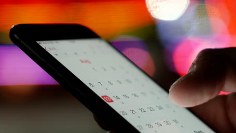 User looking at calendar dates on a smartphone - schedule for summer holiday Live Action