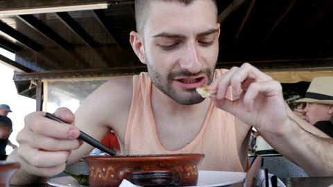 Young man eating a stew GIF