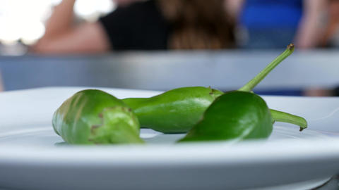 Green hot chilli peppers in a restaurant plate - eating hot jalapeno peppers - Footage