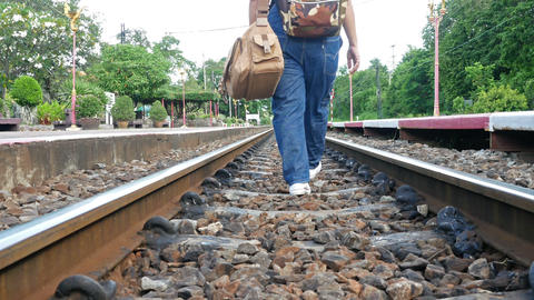 Women wearing jeans carrying luggage on a railroad track.She stumble but still Footage