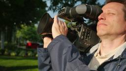 Closeup of Cameraman Focusing Camera Footage