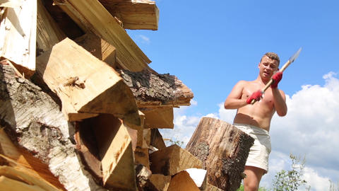A man on a hot Sunny day sweating chopping wood Footage