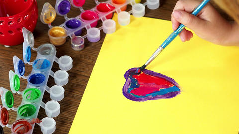 Child painting a picture. A little girl's hand painting a colorful heart on Footage