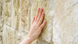 Woman sliding hand against old stone wall in slow motion. Female hand touching Footage