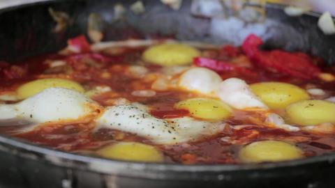 Pan cooking eggs shakshukam indian Footage