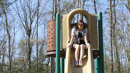 Young adult woman sliding slide, walking on children playground outside Footage