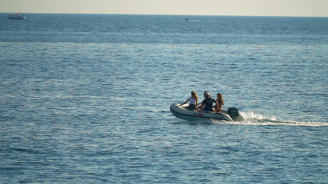 BUDVA, MONTENEGRO - JULY 26, 2018. People riding inflatable motorboat at sea Filmmaterial