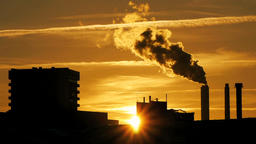 refinery plant silhouette with chimney smoke against sunset GIF