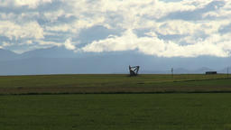 distant pump jack extracts oil among fresh field against clouds ビデオ