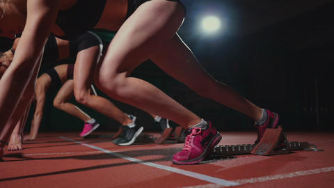 Female runners at athletics track crouching at the starting blocks before a race ビデオ