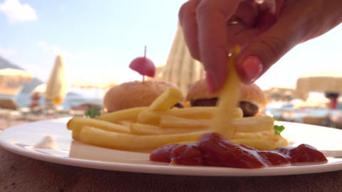 Man and woman eating french fries with ketchup on the beach Footage