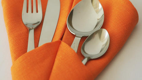 Cutlery set. Fork, knife, spoon and teaspoon in textile napkin on table GIF