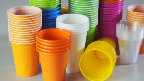 Disposable cups. Stack of colorful plastic cups on the table Footage